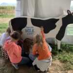 Kids practice milking a wooden cow
